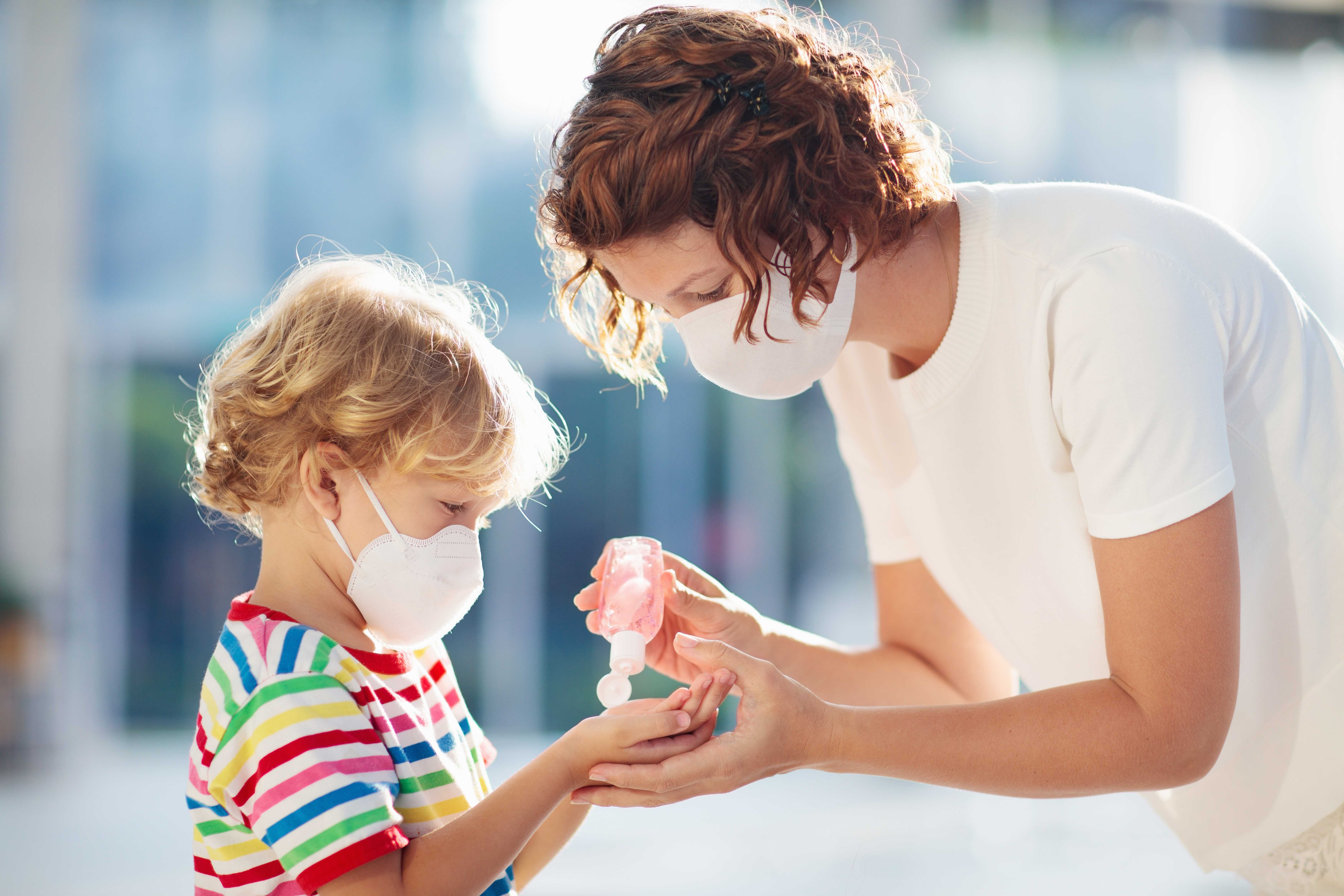 Women giving child hand sanitizer with face masks on.